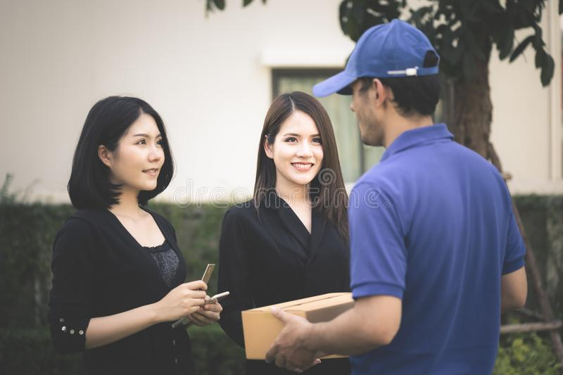 Delivery man in blue handing packages to a woman royalty free stock image
