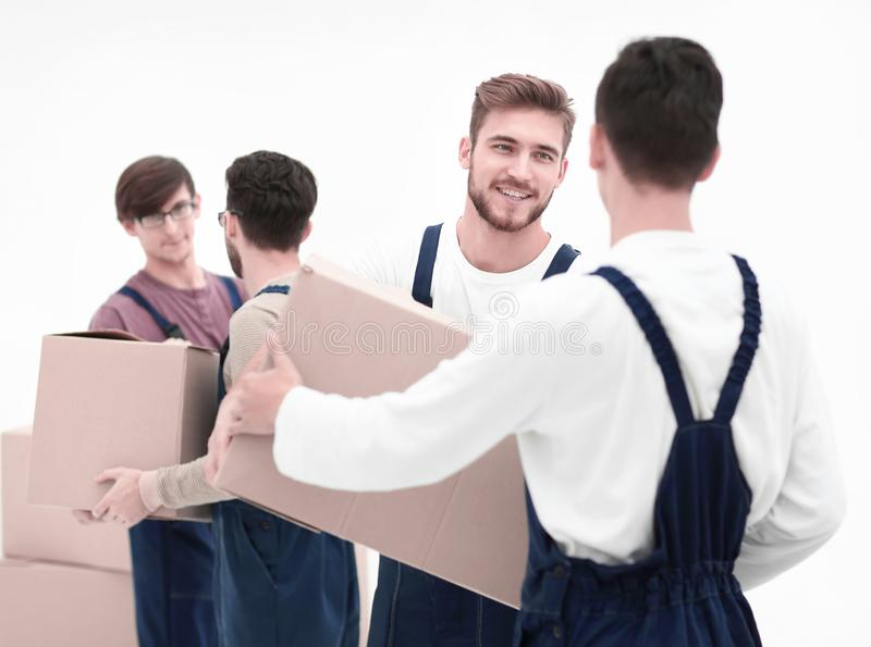 Delivery men with cardboard boxes on white background. Movers lifting stack of cardboard moving boxes isolated on white stock photo