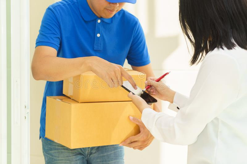 Delivery man pointing on smartphone and woman receiving package. Delivery men pointing on smartphone and women receiving package and signing on digital mobile royalty free stock photography