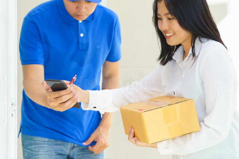 Delivery man pointing on smartphone and woman receiving package stock photos