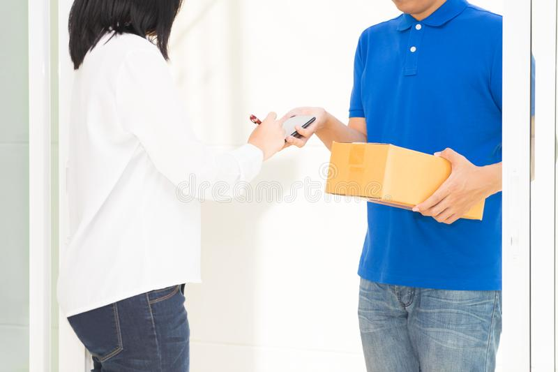Delivery man pointing on smartphone and woman receiving package. Delivery men pointing on smartphone and women receiving package and signing on digital mobile stock photo