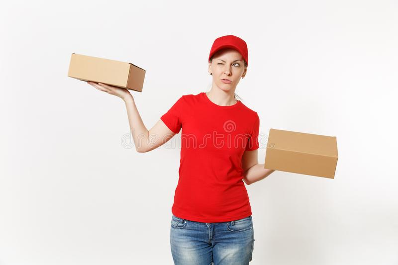 Delivery pretty woman in red uniform isolated on white background. Female in cap, t-shirt, jeans working as courier or. Dealer holding cardboard boxes stock photo