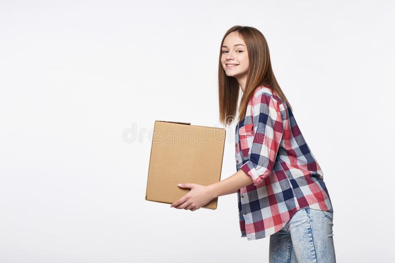 Smiling young delivering cardboard box looking at camera. Delivery, relocation and unpacking. Smiling young woman giving cardboard box looking at camera, side royalty free stock photography