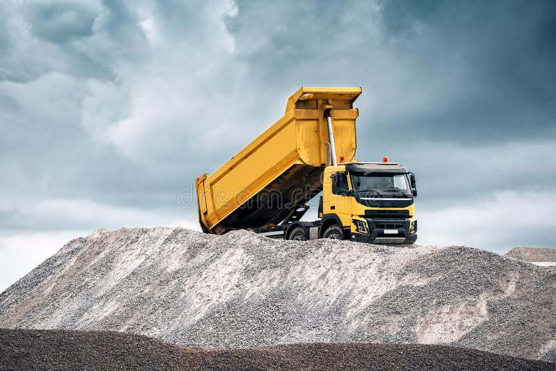 Yellow truck with raised body. Delivery of sand to the construction site by yellow truck with raised body royalty free stock photography