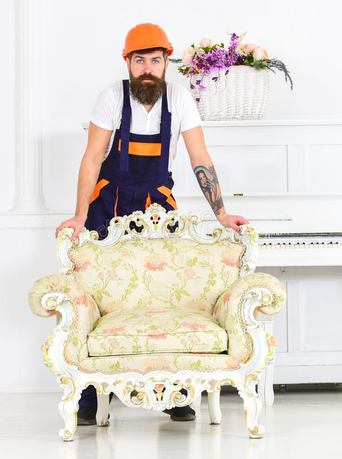 Delivery service concept. Courier delivers furniture in case of move out, relocation. Man with beard, worker in overalls royalty free stock images