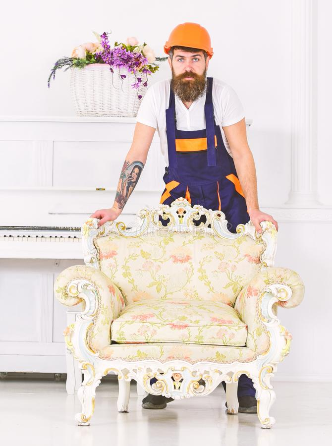 Delivery service concept. Courier delivers furniture in case of move out, relocation. Man with beard, worker in overalls royalty free stock photo