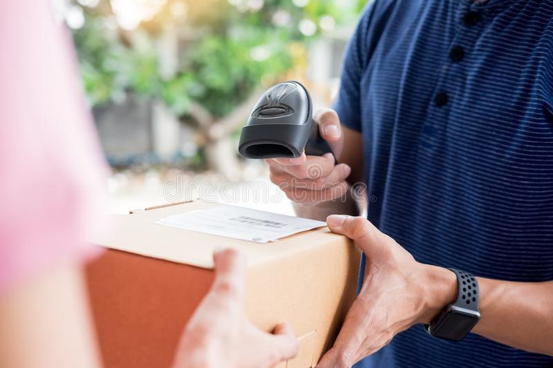 Delivery service concept, customer hand receiving a cardboard boxes parcel from delivery man at home royalty free stock photo