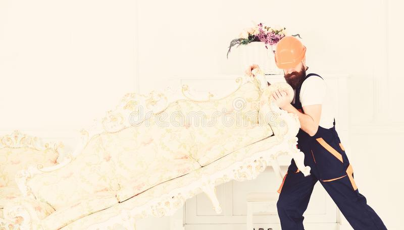 Delivery service concept. Loader moves sofa, couch. Courier delivers furniture in case of move out, relocation. Man with. Beard, worker in overalls and helmet stock photography
