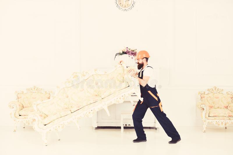 Delivery service concept. Loader moves sofa, couch. Man with beard, worker in overalls and helmet lifts up sofa, white. Background. Courier delivers furniture stock images