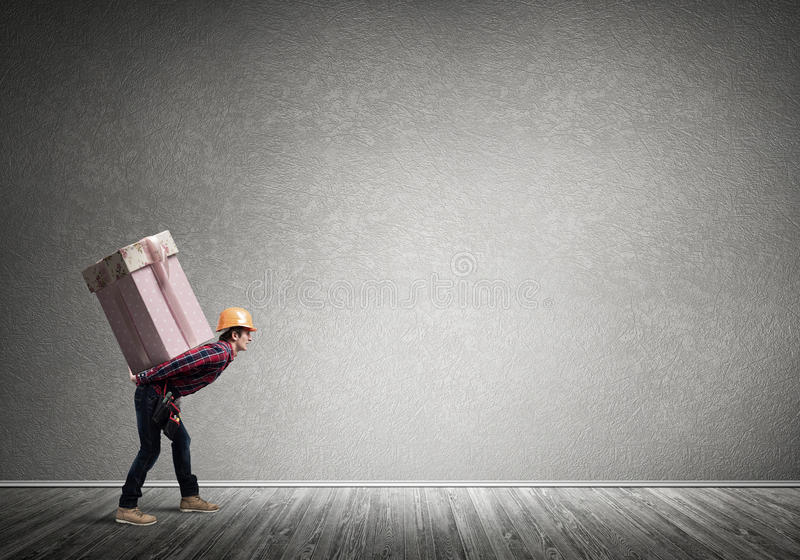 Delivery service concept. Man carrying on his back large box royalty free stock photo