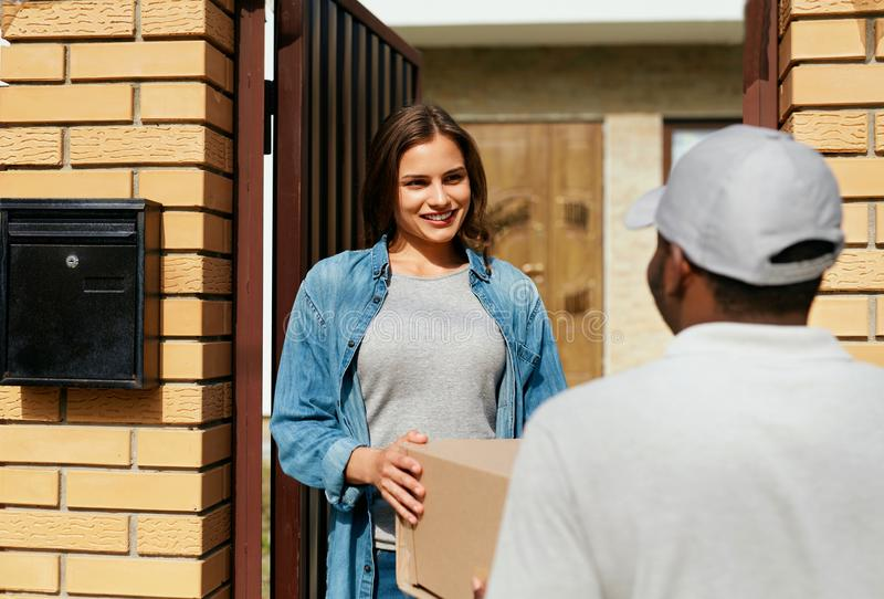 Delivery Service. Courier Delivering Package To Woman At Home. Happy Female Client Receiving Box. High Resolution royalty free stock photo