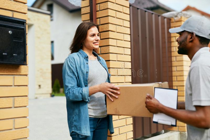 Delivery Service. Courier Delivering Package To Woman At Home. Happy Female Client Receiving Box. High Resolution stock photography