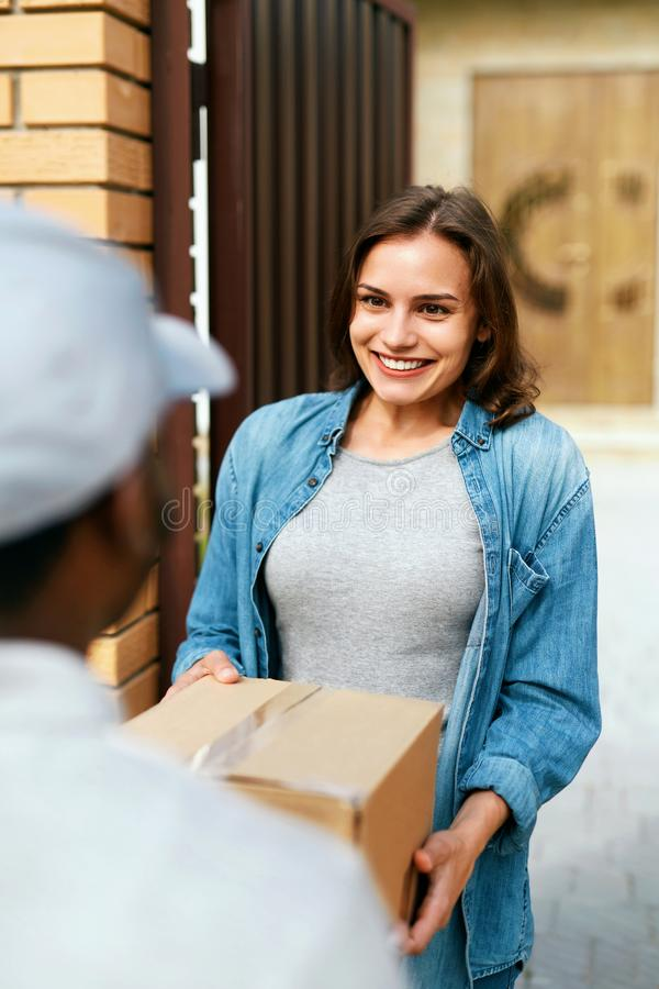 Delivery Service. Courier Delivering Package To Woman At Home. Happy Female Client Receiving Box. High Resolution stock photo