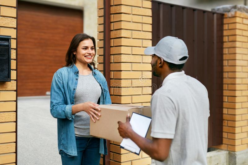 Delivery Service. Courier Delivering Package To Woman At Home. Happy Female Client Receiving Box. High Resolution stock photos