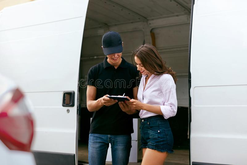 Delivery Service. Courier Delivering Package To Woman Near Car. Delivery Service. Courier Delivering Package To Woman Near Truck Car With Boxes Outdoors. High stock photography