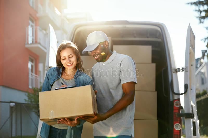 Delivery Service. Courier Delivering Package To Woman Near Car. Delivery Service. Courier Delivering Package To Woman Near Truck Car With Boxes Outdoors. Female stock photos