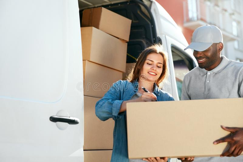Delivery Service. Courier Delivering Package To Woman Near Car. Delivery Service. Courier Delivering Package To Woman Near Truck Car With Boxes Outdoors. Female stock photo