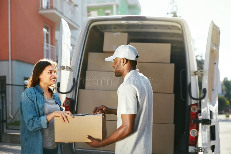 Delivery Service. Courier Delivering Package To Woman Near Car. Delivery Service. Courier Delivering Package To Woman Near Truck Car With Boxes Outdoors. High royalty free stock photo