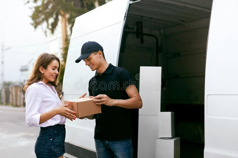 Delivery Service. Courier Delivering Package To Woman Near Car. Delivery Service. Courier Delivering Package To Woman Near Truck Car With Boxes Outdoors. High royalty free stock photos