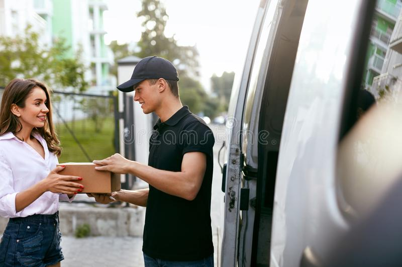 Delivery Service. Courier Delivering Package To Woman Near Car. Delivery Service. Courier Delivering Package To Woman Near Truck Car With Boxes Outdoors. High royalty free stock images