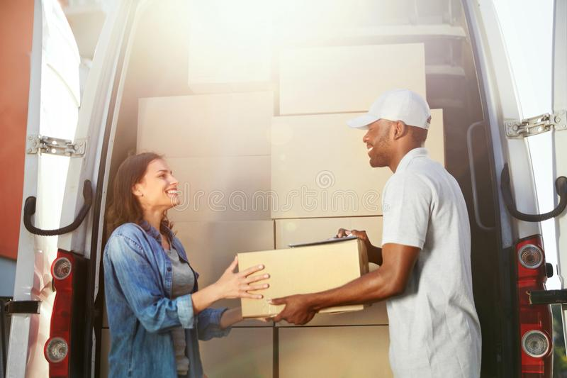 Delivery Service. Courier Delivering Package To Woman Near Car. Delivery Service. Courier Delivering Package To Woman Near Truck Car With Boxes Outdoors. High royalty free stock photography