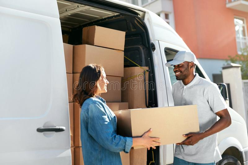 Delivery Service. Courier Delivering Package To Woman Near Car. Delivery Service. Courier Delivering Package To Woman Near Truck Car With Boxes Outdoors. High royalty free stock image