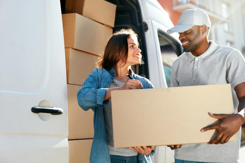Delivery Service. Courier Delivering Package To Woman Near Car. Delivery Service. Courier Delivering Package To Woman Near Truck Car With Boxes Outdoors. High stock image