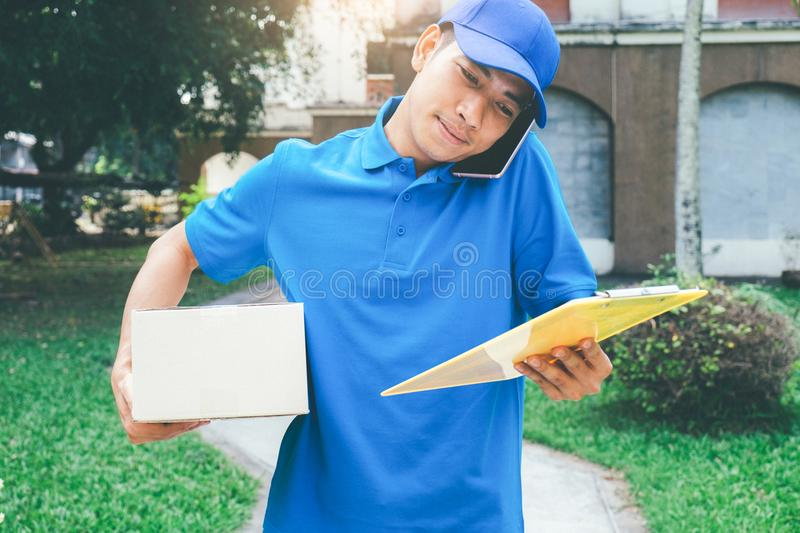 Delivery service courier standing in front of the house with box. Es and clipboard in hands royalty free stock photography