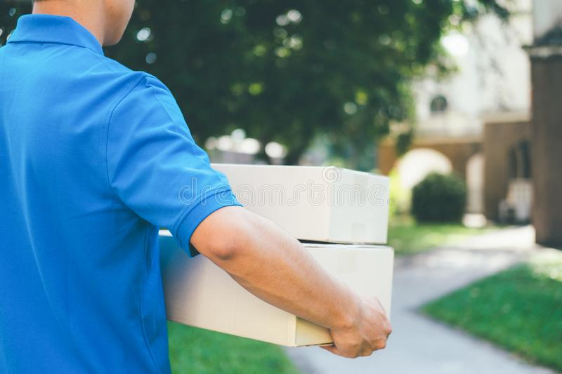 Delivery service courier standing in front of the house with box royalty free stock photos