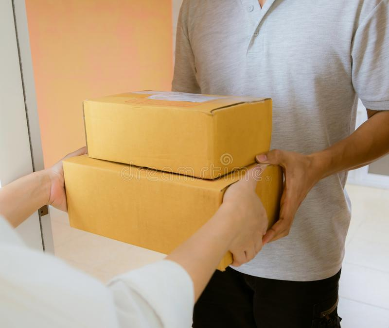 Delivery staff uniform handing a parcel box receiving parcel. From delivery royalty free stock image