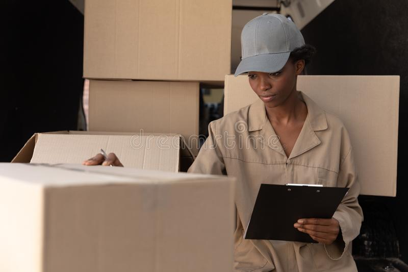 Delivery woman checking parcel near van outside the warehouse. Front view of delivery woman checking parcel near van outside the warehouse. This is a freight stock images