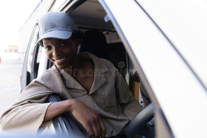 Delivery woman looking at camera while sitting in front seat of van outside the warehouse. Happy delivery woman looking at camera while sitting in front seat of royalty free stock image