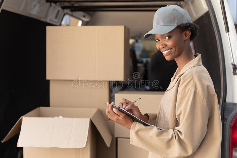 Delivery woman looking at camera while writing on clipboard near van outside the warehouse royalty free stock images