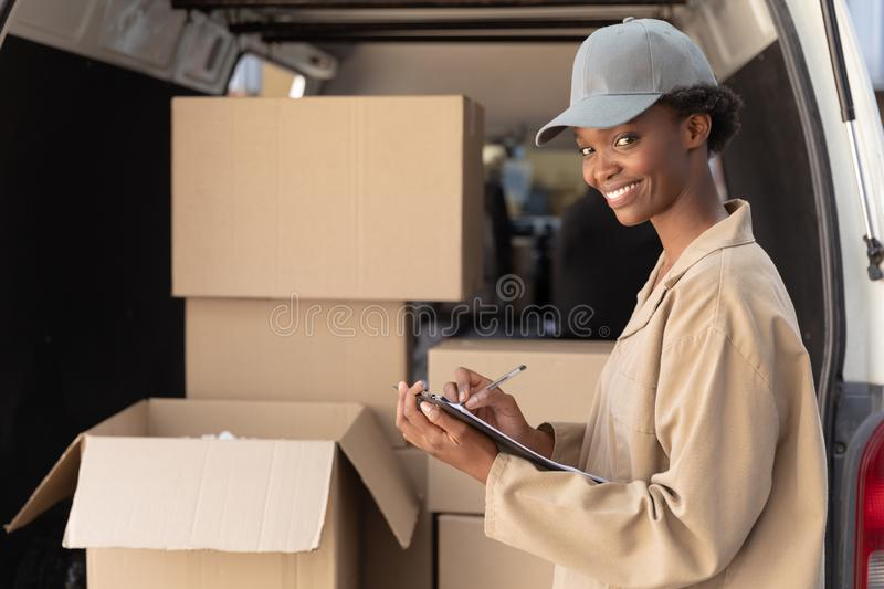 Delivery woman looking at camera while writing on clipboard near van outside the warehouse royalty free stock photos
