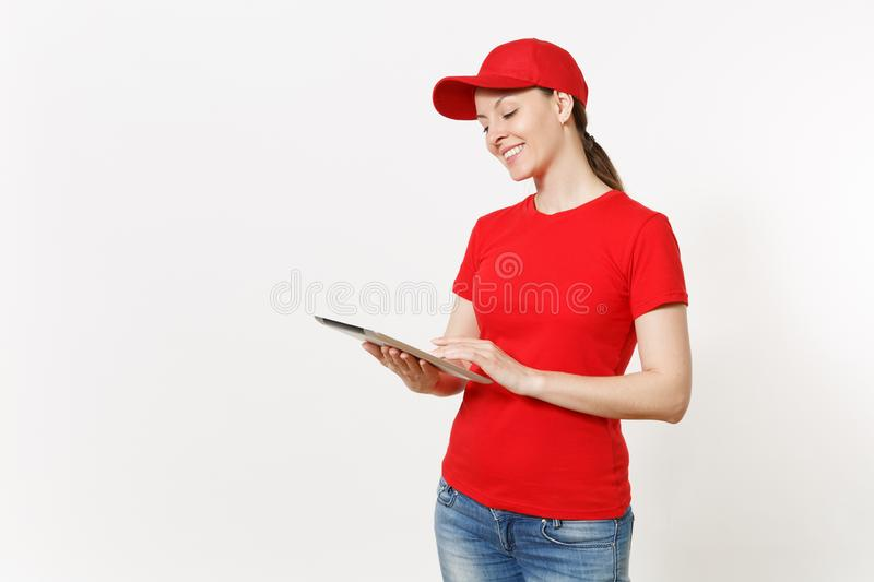 Delivery woman in red uniform isolated on white background. Female in cap, t-shirt, jeans working as courier or dealer. Holding tablet pc computer with blank royalty free stock image