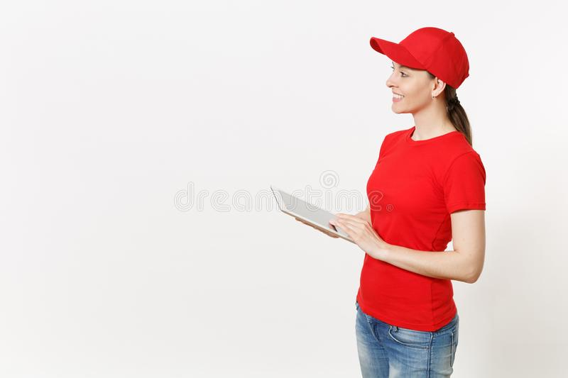 Delivery woman in red uniform isolated on white background. Female in cap, t-shirt, jeans working as courier or dealer. Holding tablet pc computer with blank royalty free stock photo