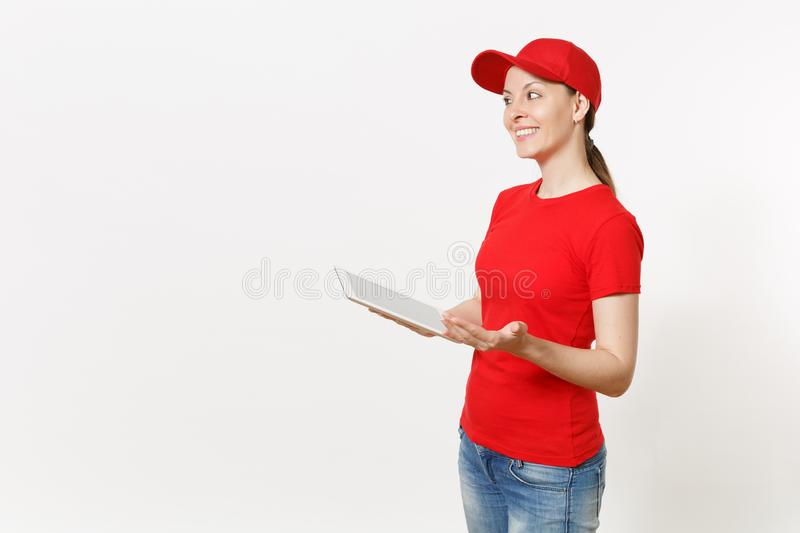 Delivery woman in red uniform isolated on white background. Female in cap, t-shirt, jeans working as courier or dealer. Holding tablet pc computer with blank royalty free stock images