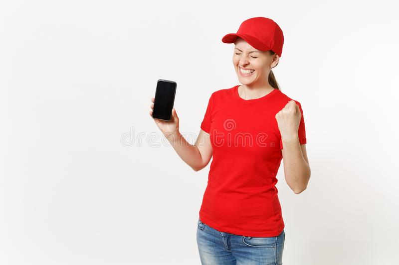 Delivery woman in red uniform isolated on white background. Female in cap, t-shirt, jeans working as courier or dealer. Showing on camera mobile phone with royalty free stock image