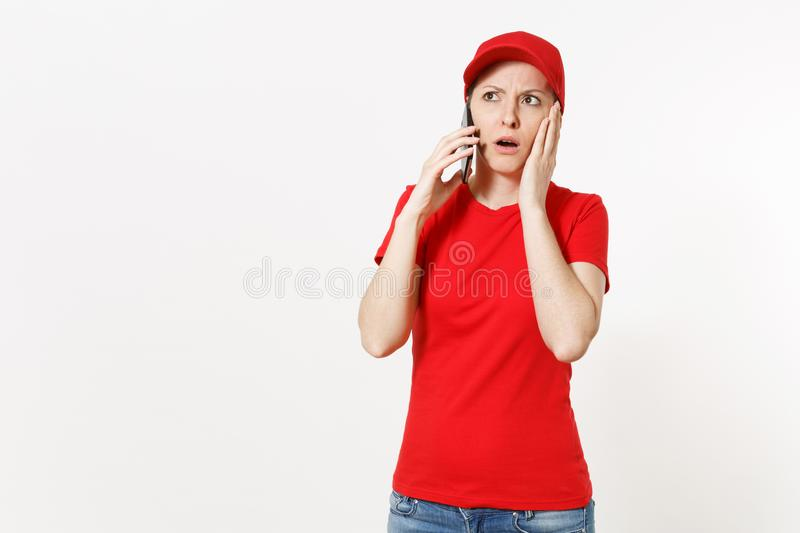 Delivery woman in red uniform isolated on white background. Female in cap, t-shirt, jeans working as courier or dealer. Talking on mobile phone, speaking stock image