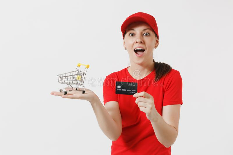 Delivery woman in red uniform isolated on white background. Female courier or dealer in cap, t-shirt holding supermarket. Grocery push cart for shopping, credit stock photography