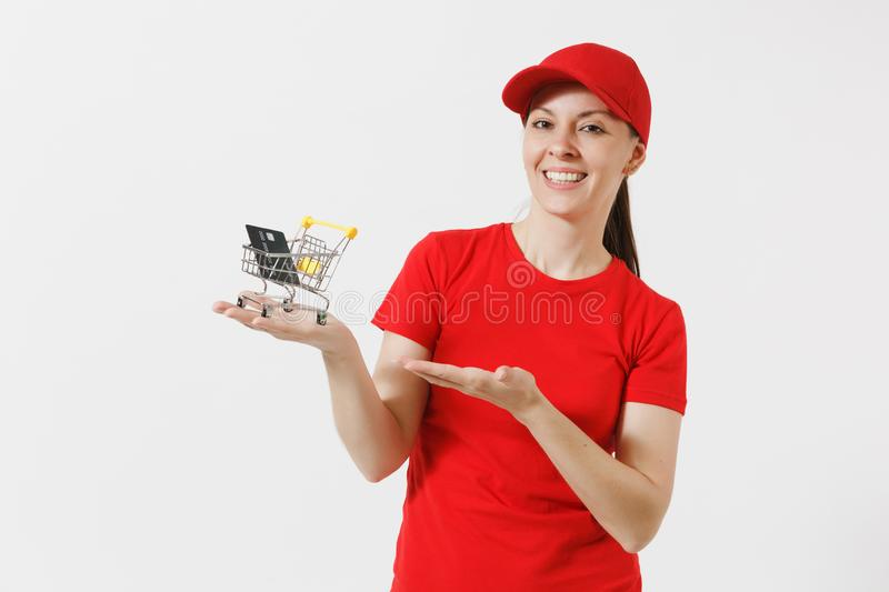 Delivery woman in red uniform isolated on white background. Female courier or dealer in cap, t-shirt holding supermarket. Grocery push cart for shopping, credit stock images