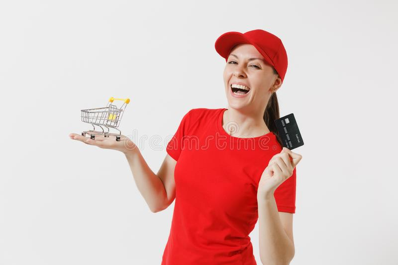 Delivery woman in red uniform isolated on white background. Female courier or dealer in cap, t-shirt holding supermarket. Grocery push cart for shopping, credit royalty free stock images