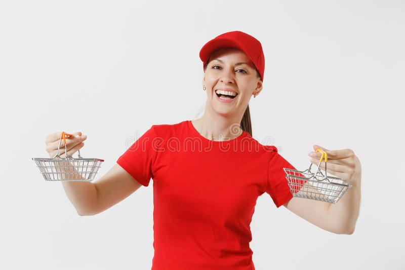 Delivery woman in red uniform isolated on white background. Female courier or dealer in cap, t-shirt, jeans holding. Metal grocery basket for shopping in stock photography