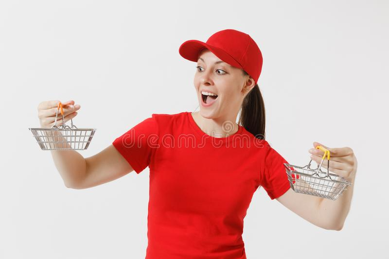 Delivery woman in red uniform isolated on white background. Female courier or dealer in cap, t-shirt, jeans holding. Metal grocery basket for shopping in royalty free stock image