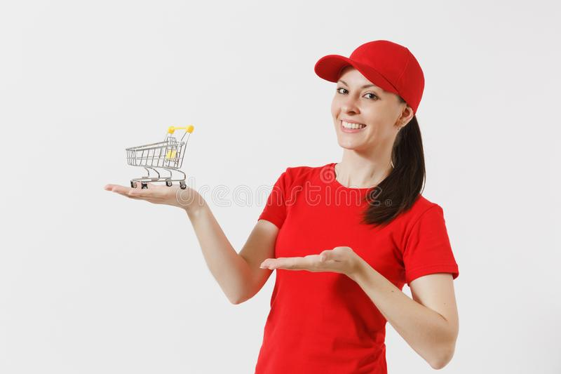 Delivery woman in red uniform isolated on white background. Female courier or dealer in cap, t-shirt, jeans holding. Supermarket grocery push cart for shopping royalty free stock photography
