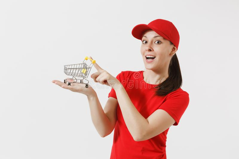 Delivery woman in red uniform isolated on white background. Female courier or dealer in cap, t-shirt, jeans holding. Supermarket grocery push cart for shopping royalty free stock photos