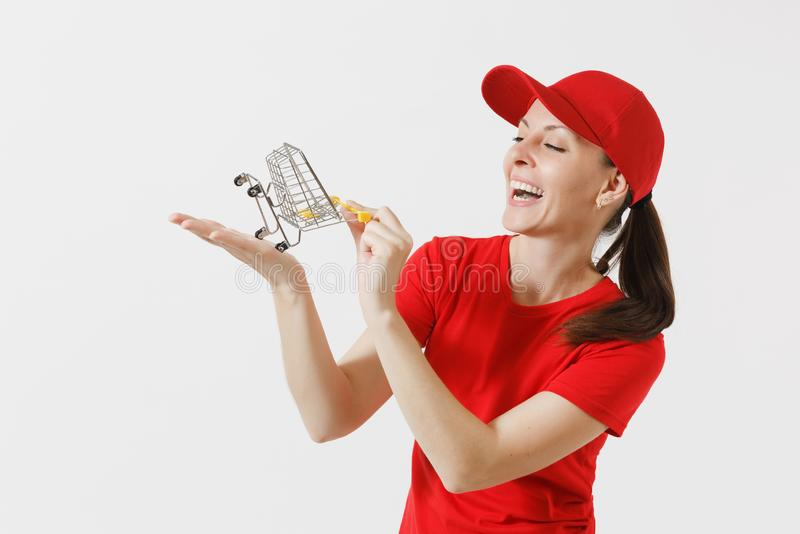 Delivery woman in red uniform isolated on white background. Female courier or dealer in cap, t-shirt, jeans holding. Supermarket grocery push cart for shopping royalty free stock image