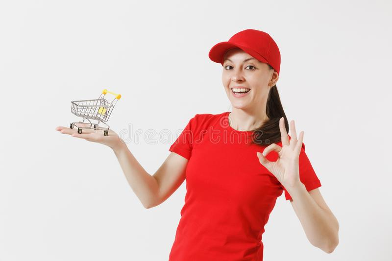 Delivery woman in red uniform isolated on white background. Female courier or dealer in cap, t-shirt, jeans holding. Supermarket grocery push cart for shopping royalty free stock images