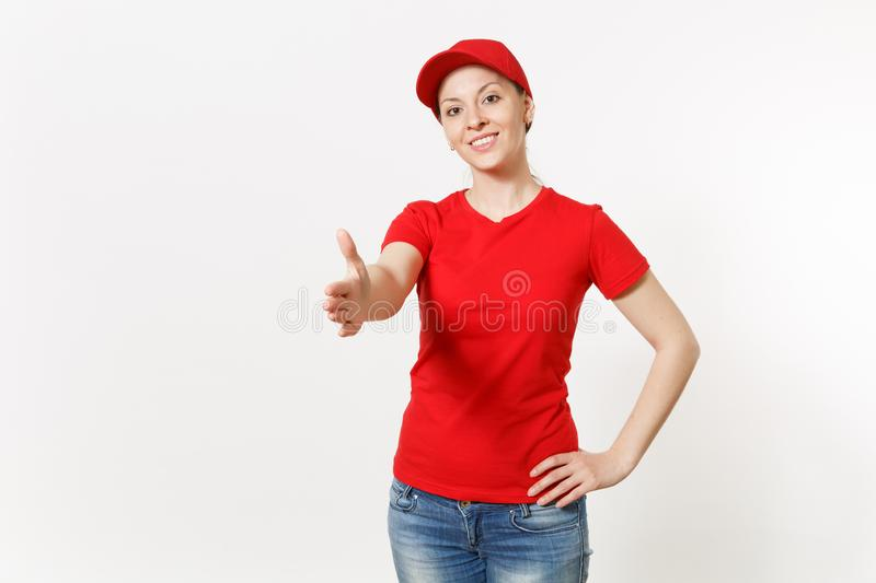 Delivery woman in red uniform isolated on white background. Friendly female in cap, t-shirt, jeans working as courier. Looking camera standing with outstretched stock photography