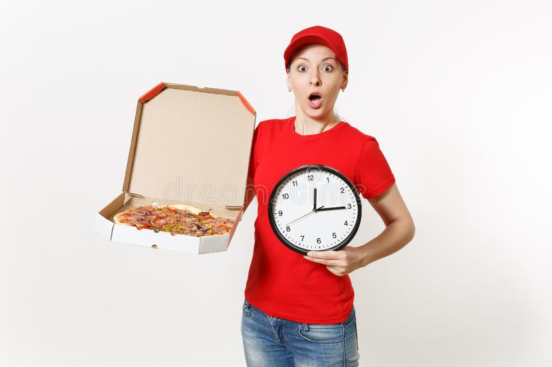 Delivery woman in red uniform isolated on white background. Pretty female in cap, t-shirt, jeans working as courier. Holding italian pizza in cardboard flatbox royalty free stock image